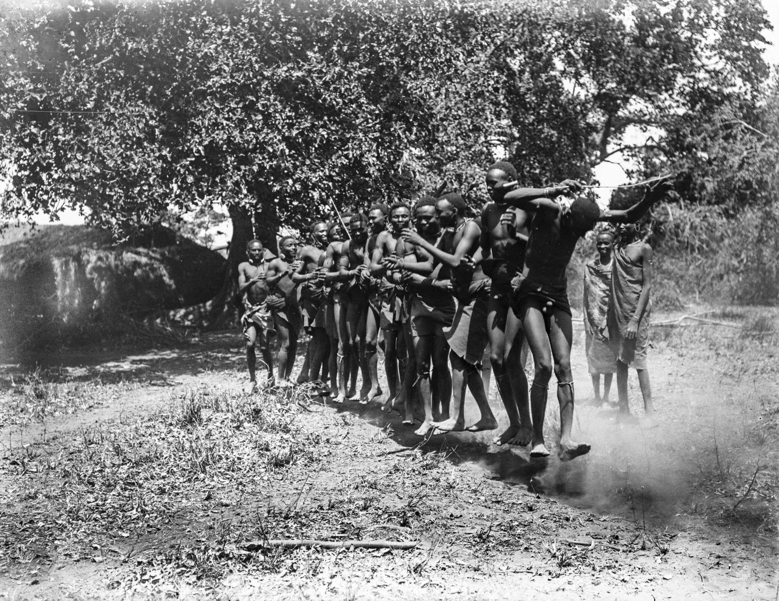 07. Группа людей басонжо во время танца у лагеря Ндалалани. Танцоры прыгают на два фута высотой, вытянув тела