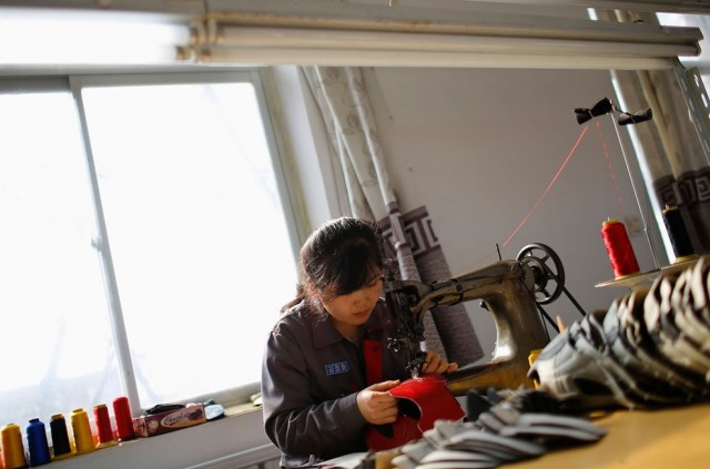 A North Korean worker sews inside a temporary soccer shoe factory at a rural village on the edge of