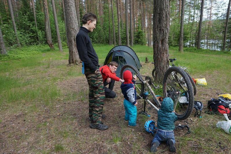 папы и дети чинят велосипед в походе
