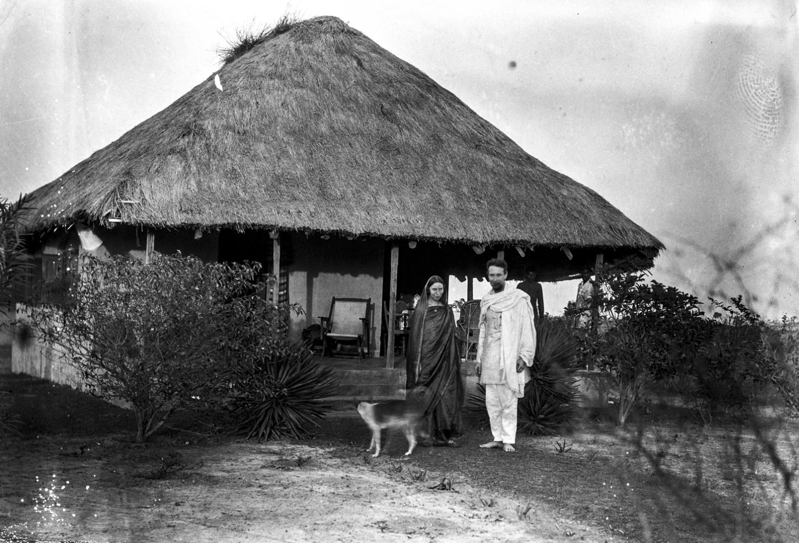 1334. Шантиникетан. Два человека с собакой в передней части дома