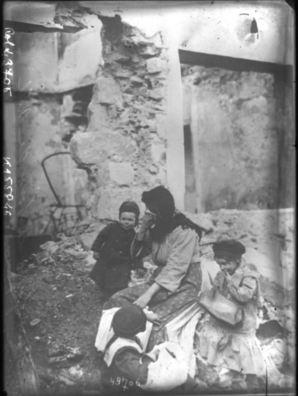 1914. Бездомные на Рождество. Женщина плачет среди руин, в окружении трех маленьких детей