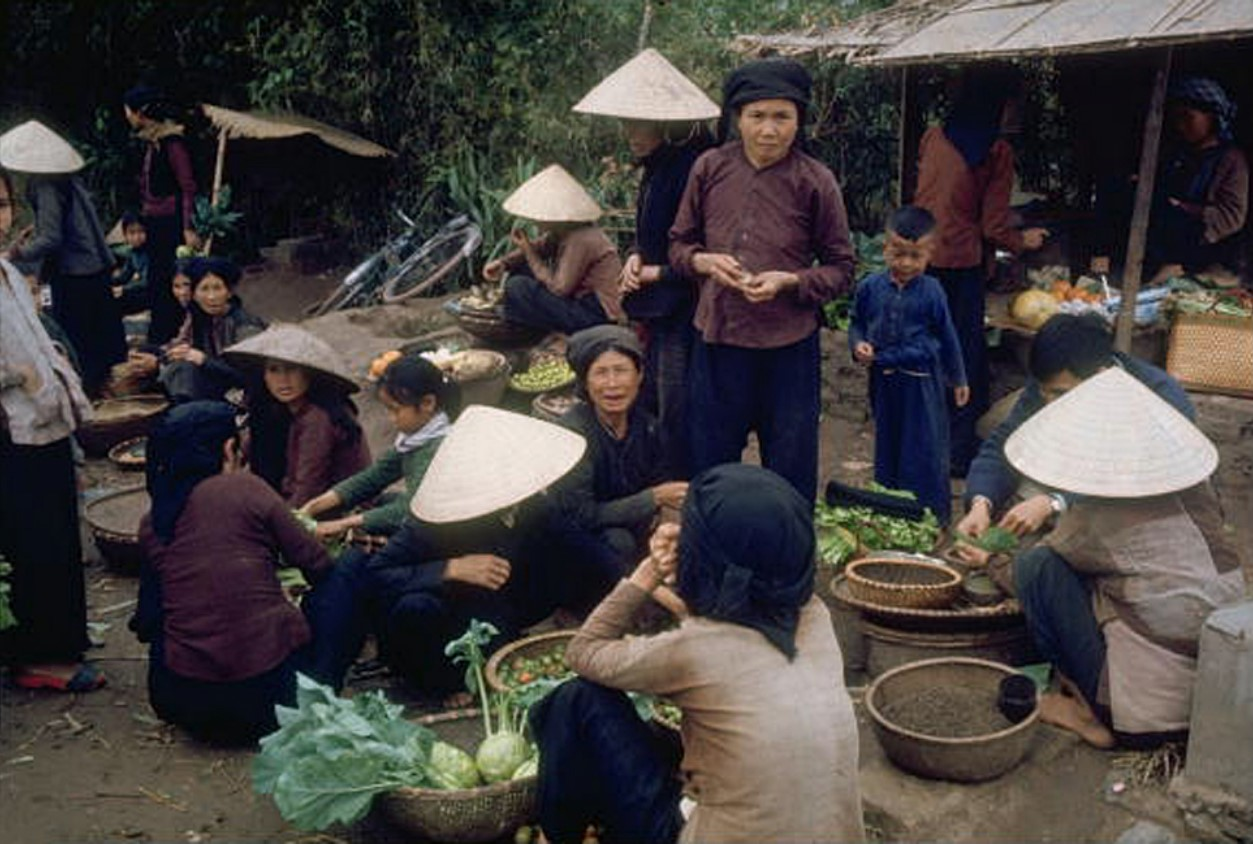 Женщины в традиционных конических шляпах продают рыбу и овощи на рынке