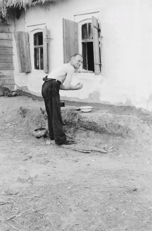 Солдат умывается возле крестьянского дома