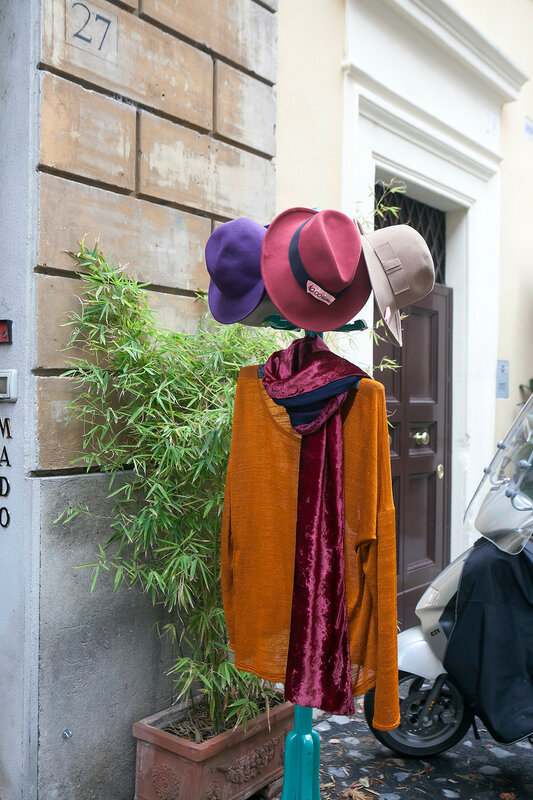 Brown cloak and colored hats on a hanger for sale at the entrance to the store