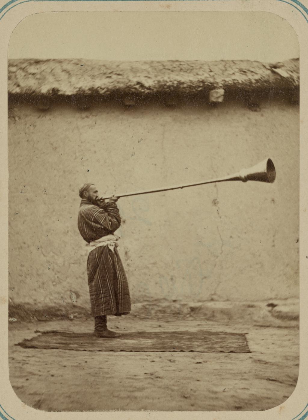 Музыканты. Мужчина за игрой на карнае, инструменте с длинным стволом, напоминающем трубу.