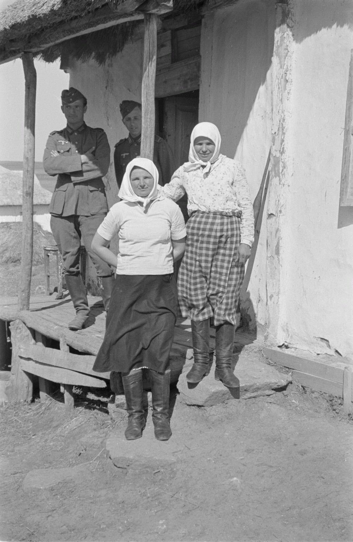 Два солдата у входа в крестьянскую хижину