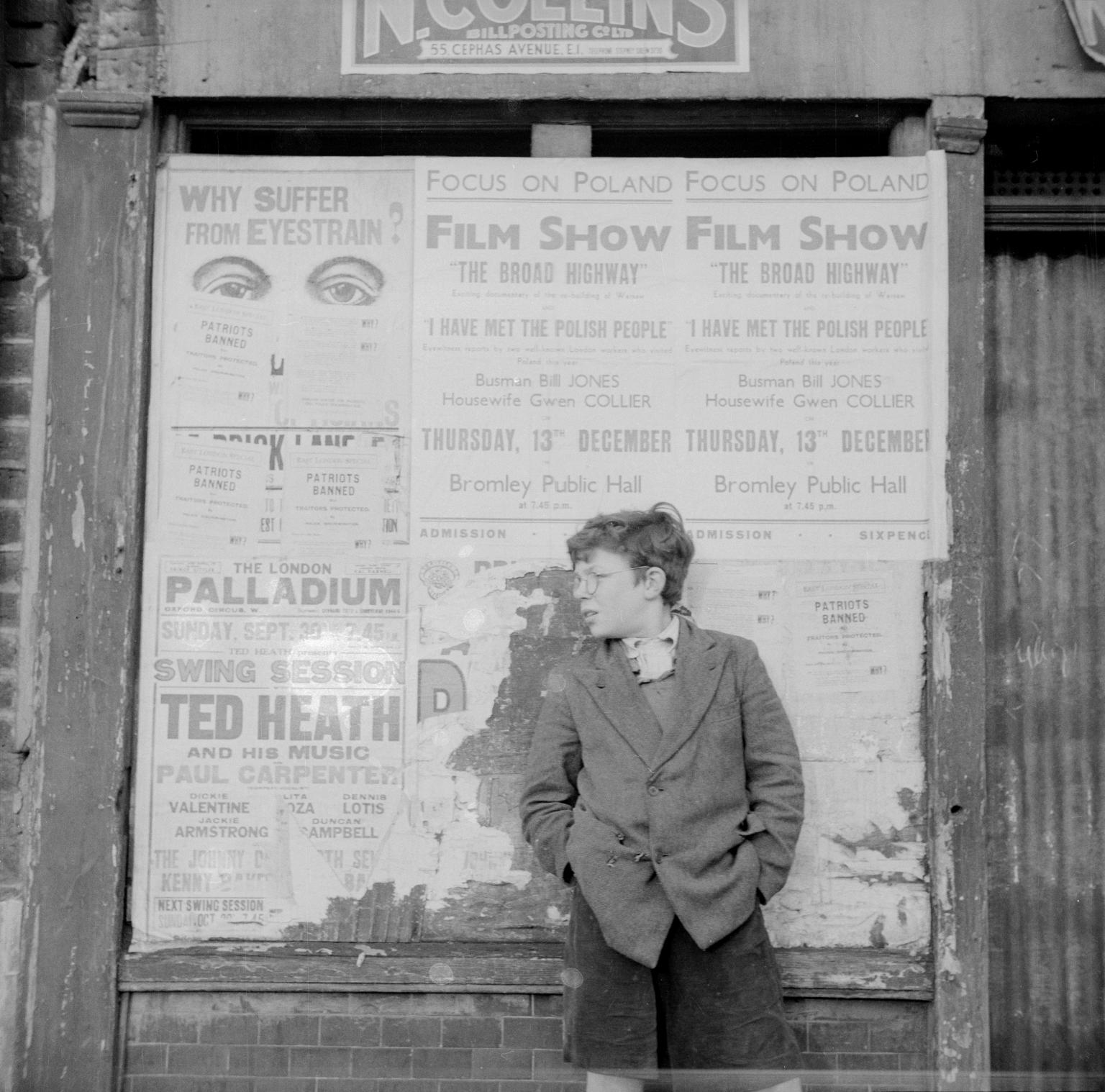 Питер Самуэльс перед рекламными плакатами. 951