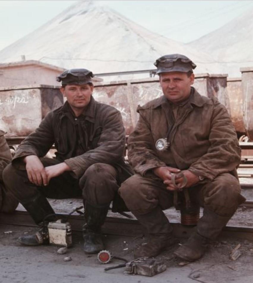 Два шахтера, сидящие на рельсах перед вагонами