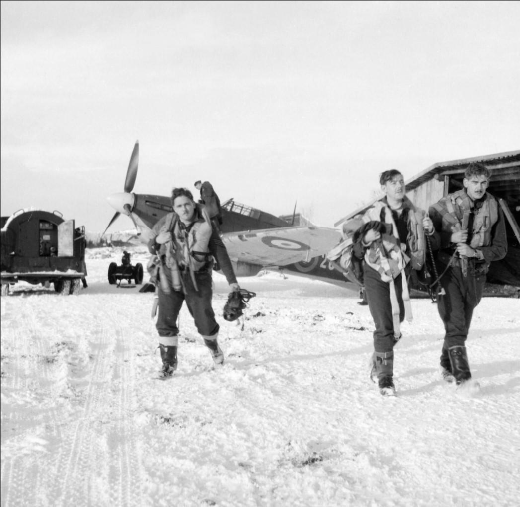 Пилоты идут по снегу в штаб-квартиру, чтобы сообщить дежурному офицеру о выполнение миссии по сопровождению советских бомбардировщиков к цели