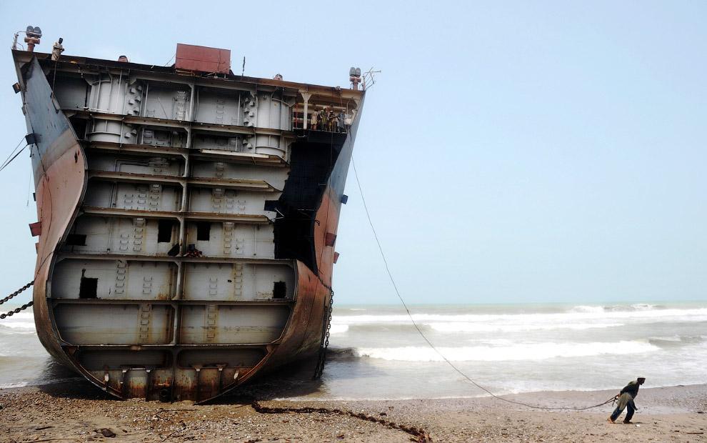 3. Весь труд здесь ручной. Вот рабочие с помощью горелки отрезают от корабля кусок металла. Пакистан