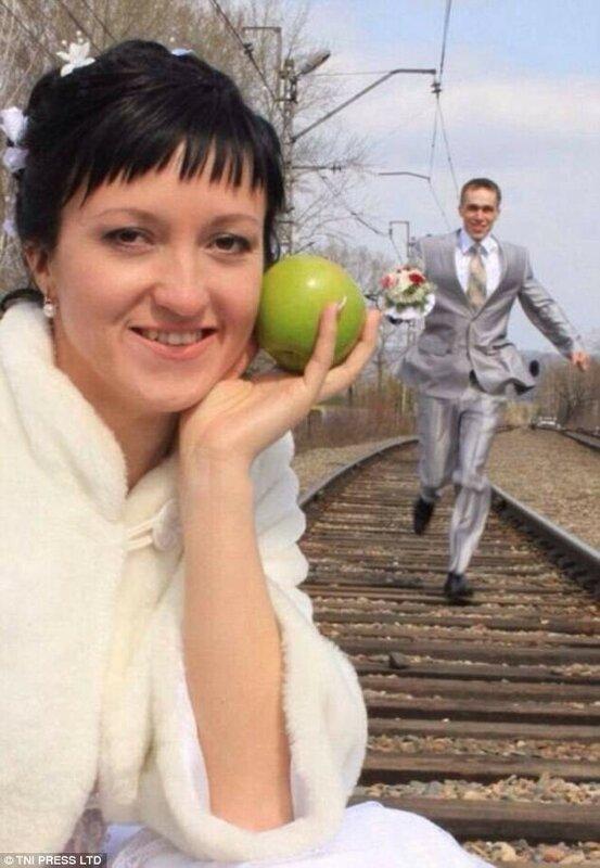 Невеста позирует с яблоком, жених бежит по рельсам. Почему бы и нет.