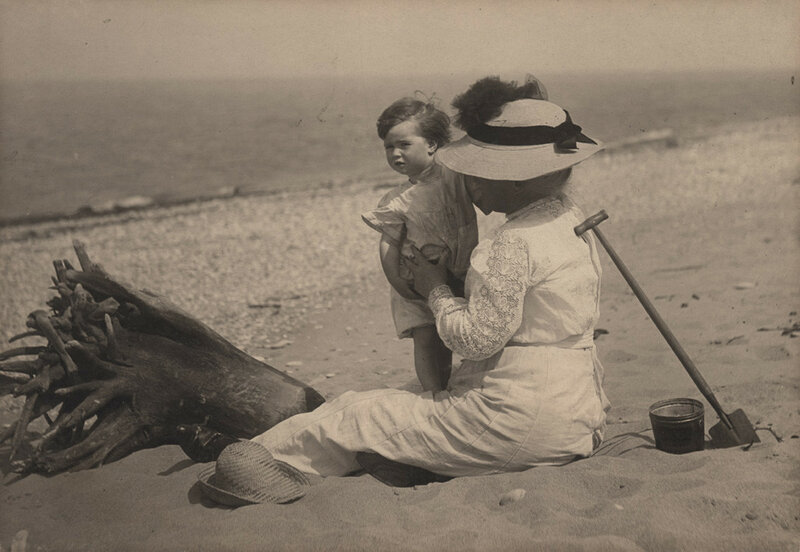 Woman with child at beach, date unknown