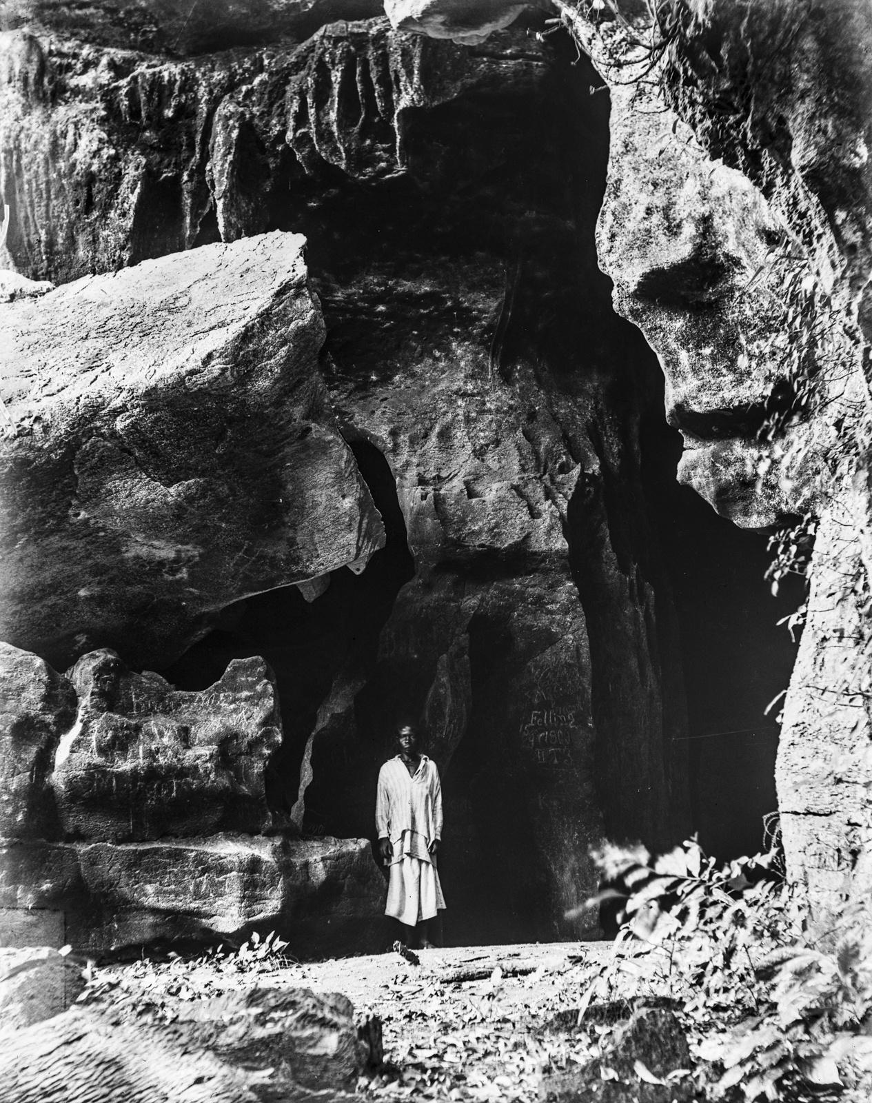 15. Человек во входе в пещеру Сига около Танги