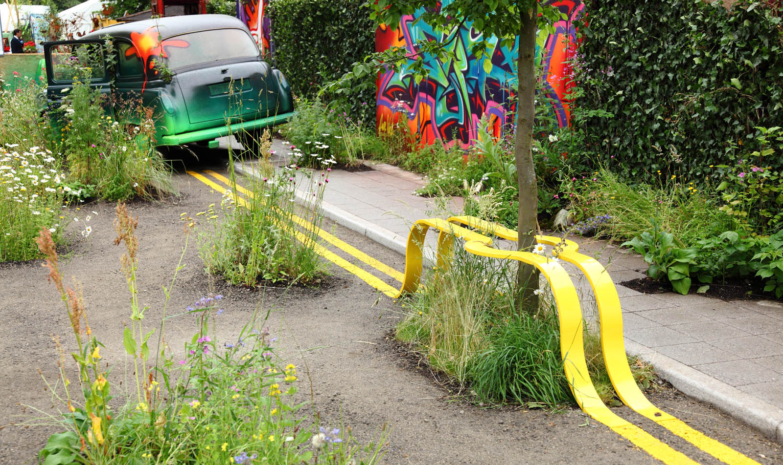 Yellow Street Lines Form a Park Bench Around a Tree in this Temporary Green Space by The Edible Bus Stop (3 pics)