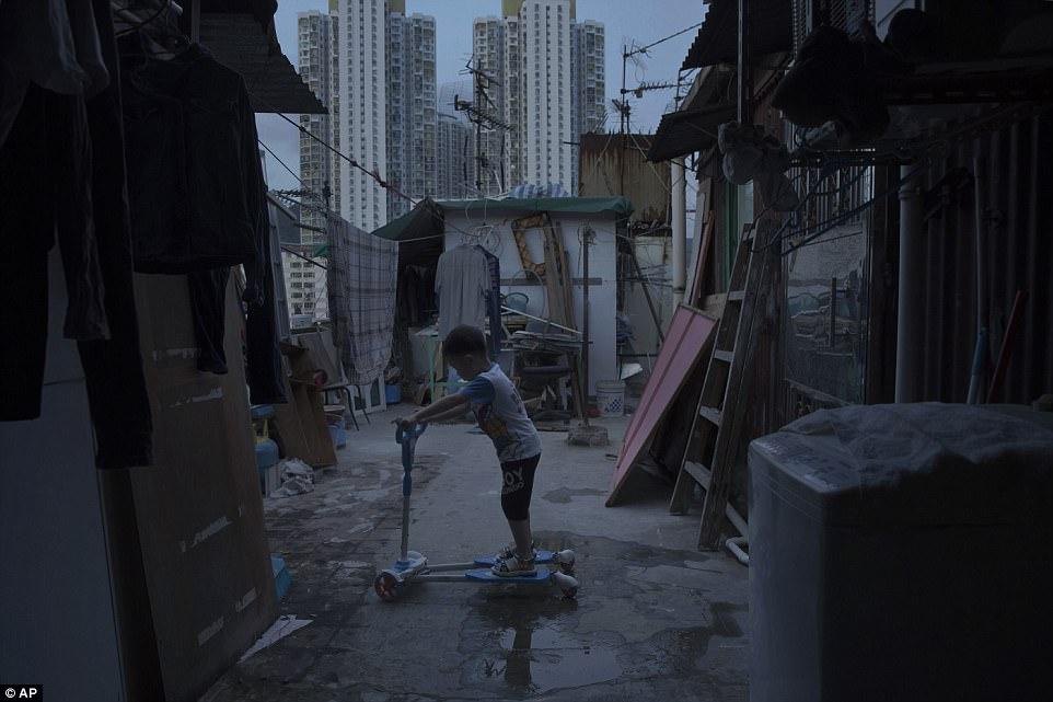 5-летний мальчик играет около крошечного дома, сделанного из бетона и гофрированного металла, где он