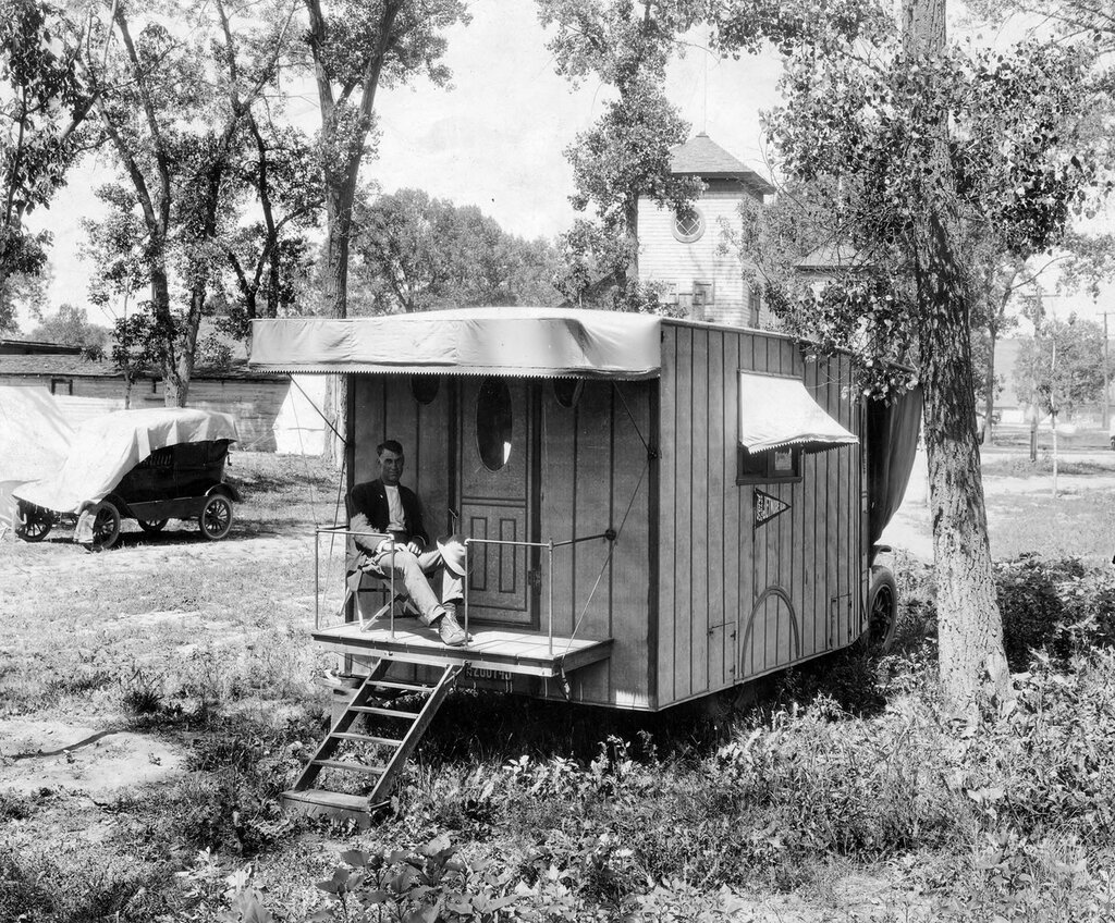 """A man sits on the porch of his camper in the auto camp at Overland Park in the Overland neighborhood of Denver, Colorado. The license plates are from Kansas, and a banner on the side of the vehicle reads """"Jetmore, Kan"""". [between 1920 and 1931]"""