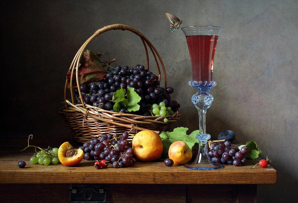 C корзиной винограда и бокалом вина.