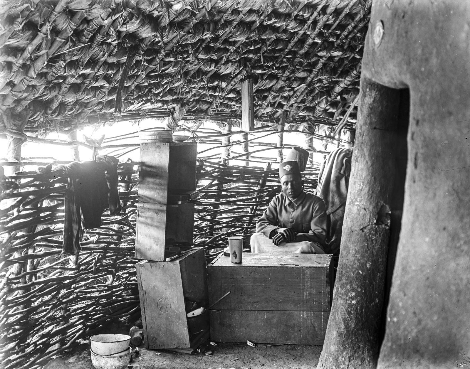 34. Внутренняя часть деревенской круглой хижины в горах Паре. Джембе (староста деревни) сидит за ящиками, которые служат ему столом