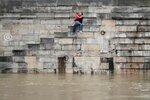 Пара целуется на ступеньках набережной Сены в Париже, 1 июня 2016 года. Прошедший накануне циклон вызвал наводнения, и река вышла из своих берегов. Фото: Charles Platiau / Reuters