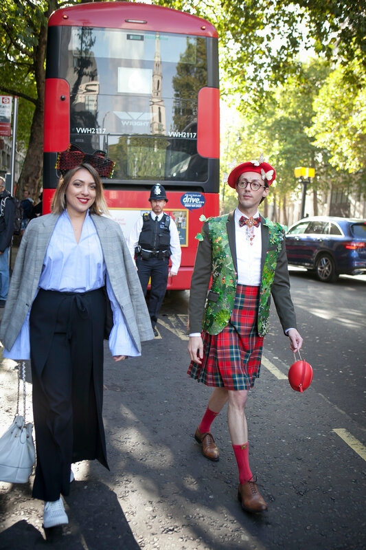 LONDON, ENGLAND - September 15, 2017 Beautiful and stylish woman and man in red beret and skirt posing during the London Fashion Week. outside Eudon Choi
