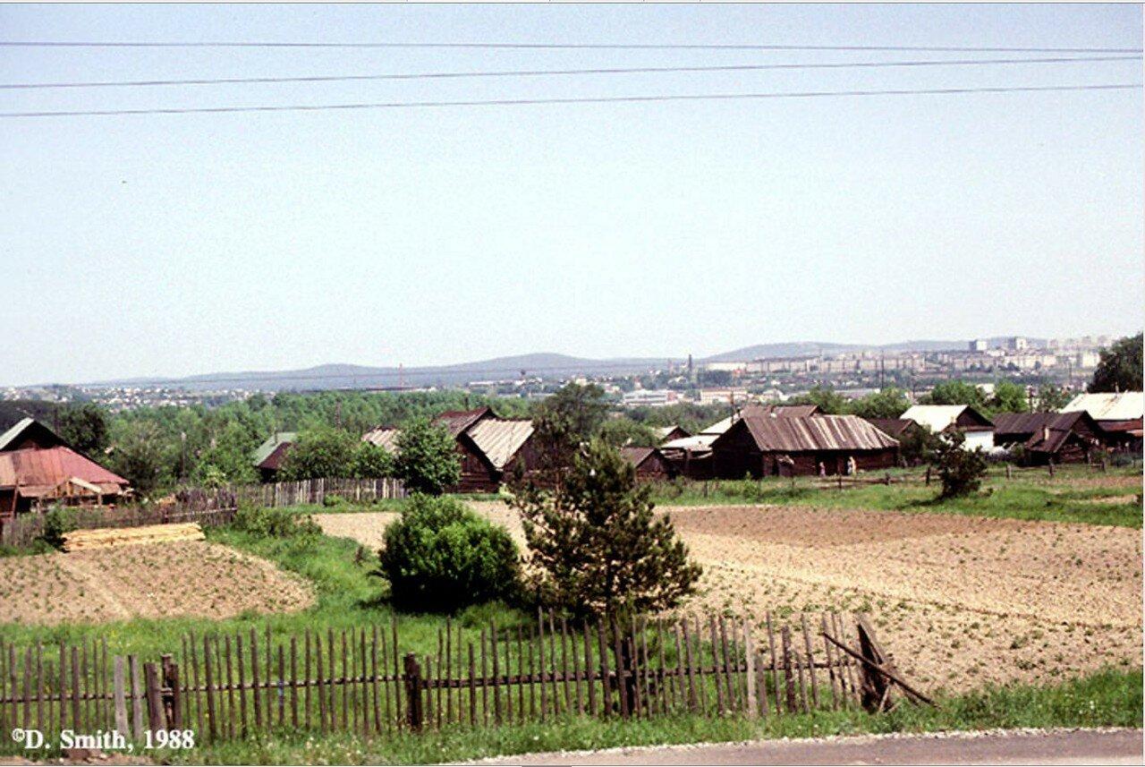 Вид сибирской деревне из вагона поезда на Транссибирской магистрали