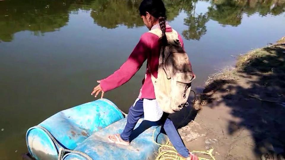 Школьники из Индии используются паром из пластиковых бочек, чтобы попасть в школу