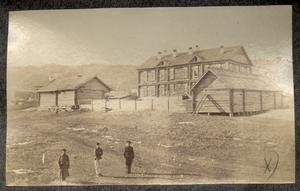 Два охранника с каторжанином на фоне тюремного поселения