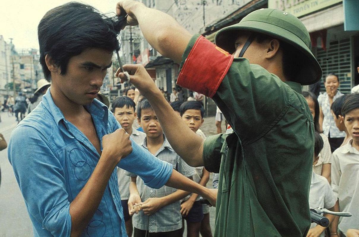 Вьетконговец портит сделанную по западной моде прическу молодому человеку и разрезает ему рубашку. 30 апреля 1975
