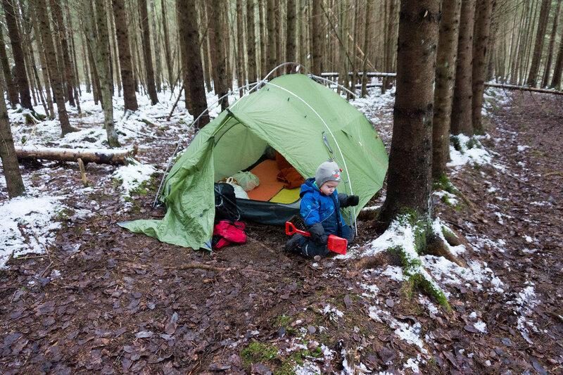 ребенок у палатки в походе в лес зимой