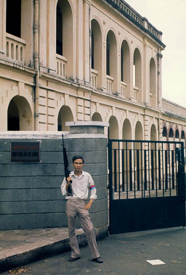 Милиционер Национального фронта освобождения перед зданием после падения города 30 апреля 1975 года