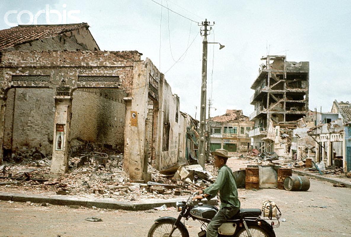 Район Тёлон после того, как большая часть боёв закончилась. Мужчина проезжает мимо переулка и сильно поврежденного здания на мопеде. 10 июня