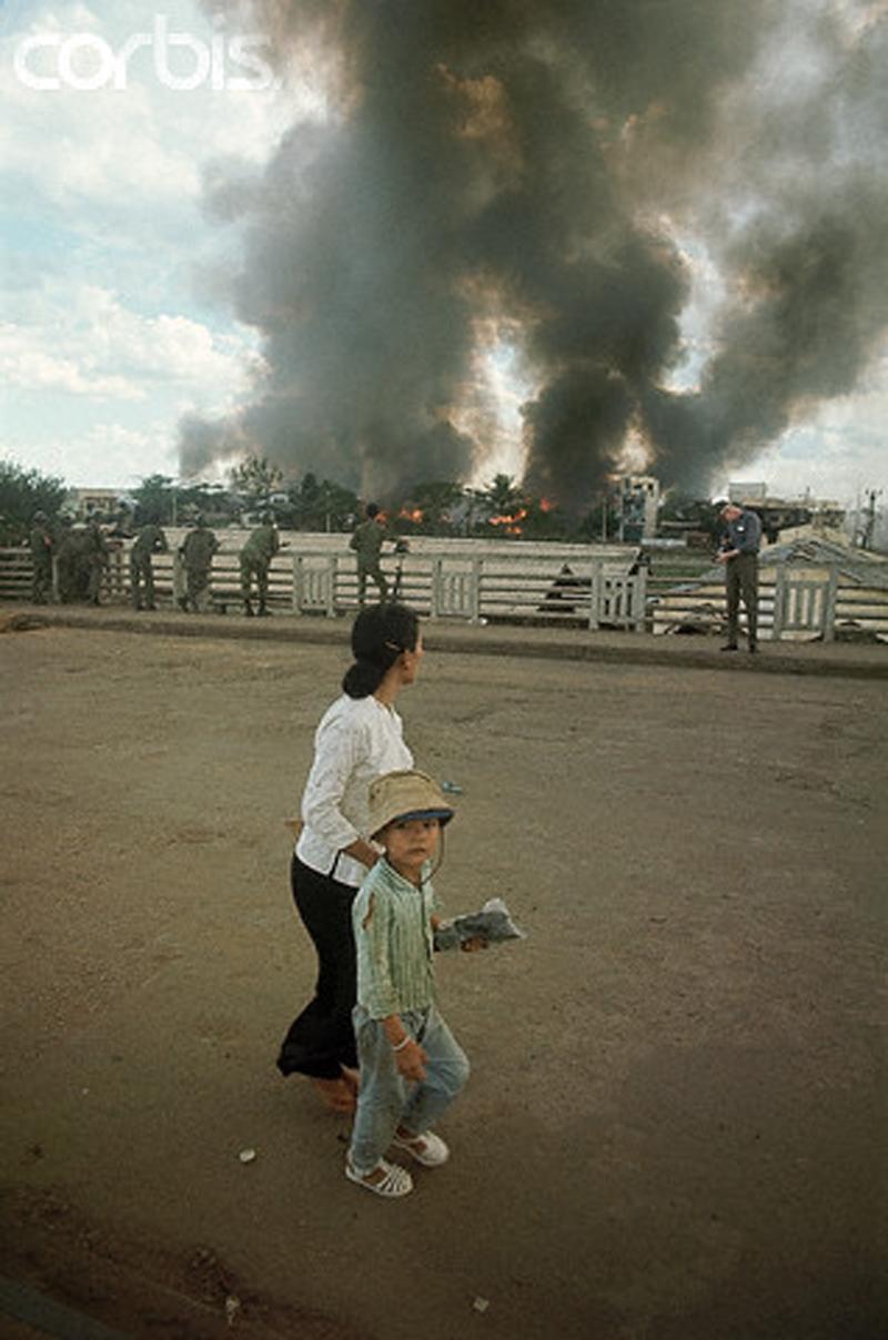 Мать и ребенок смотрят, как горит Таншоннят после нападения вьетконговцев. 6 мая