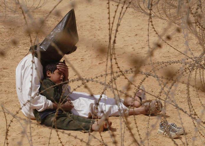 Ирак. Мужчина успокаивает своего 4-летнего сына в центре содержания военнопленных, в базовом лагере