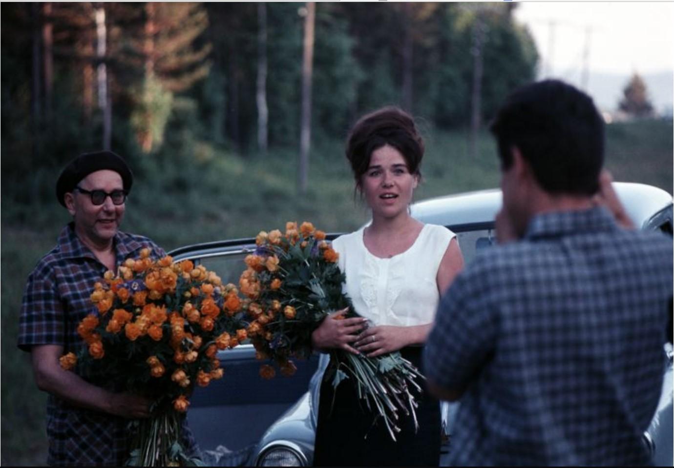 Женщина и мужчина с большими букетами жарков (в оригинале розами)