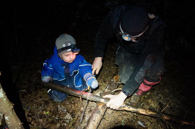 папа и ребенок пилят ствол пилой Fiskars в походе