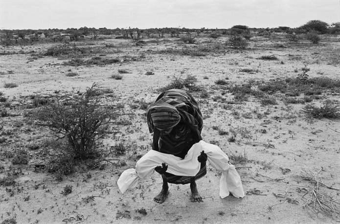 Бардера, Сомали. Мать несет своего мертвого ребенка, завернутого в саван в соответствии с мусульманс