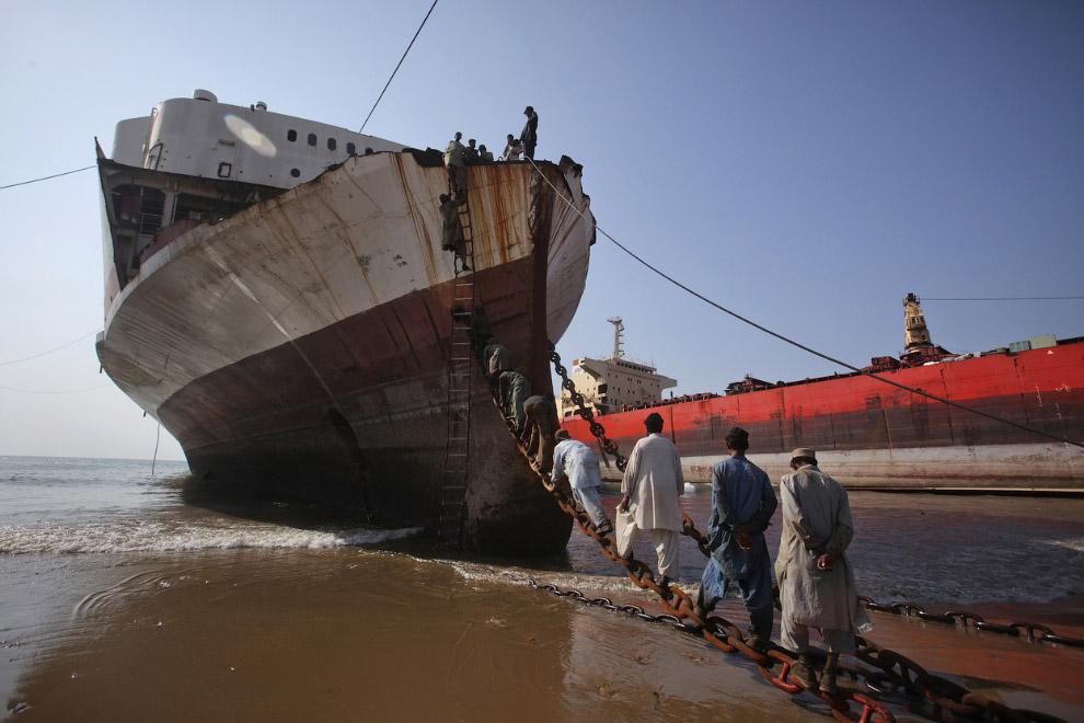 25. Рабочие выкатывают нефтяные бочки с корабля на берег, Читтагонг, Бангладеш, 24 июля 2008. (Фото