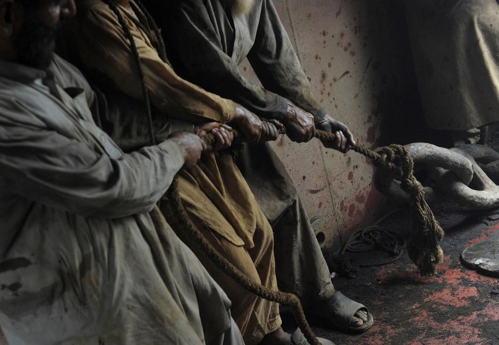 29. Пакистанский рабочий спускается с корабля по якорной цепи, Гаддани, 10 июля 2012. (Фото Roberto