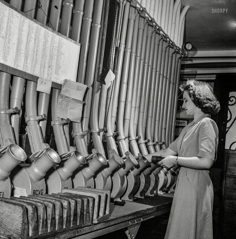 June 1943. Washington, D.C. Miss Helen Ringwald, employee at the Western Union telegraph office, works with the pneumatic tubes through which messages are sent to branches in other parts of the city for delivery.