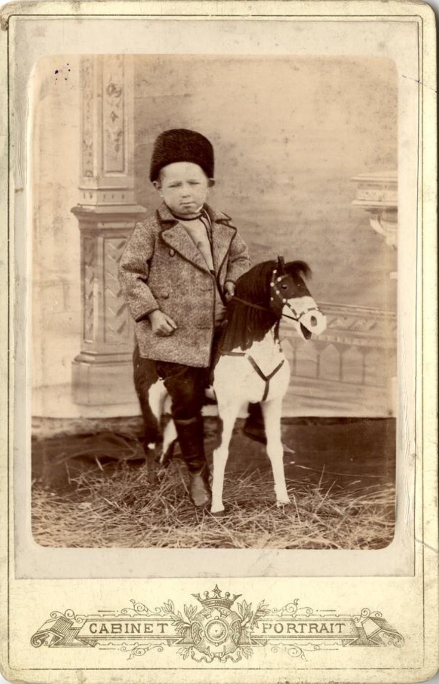 Портрет мальчика, сидящего на игрушечном коне