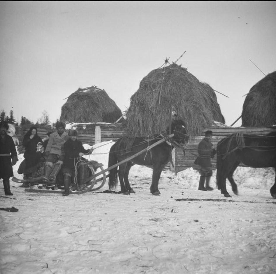 Деревенские жители на фоне снопов сена