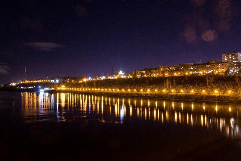 Подсвеченная отражающимися в реке фонарями набережная города Кирова в районе старого моста, огни домов и церквей, телевышка с красными огоньками