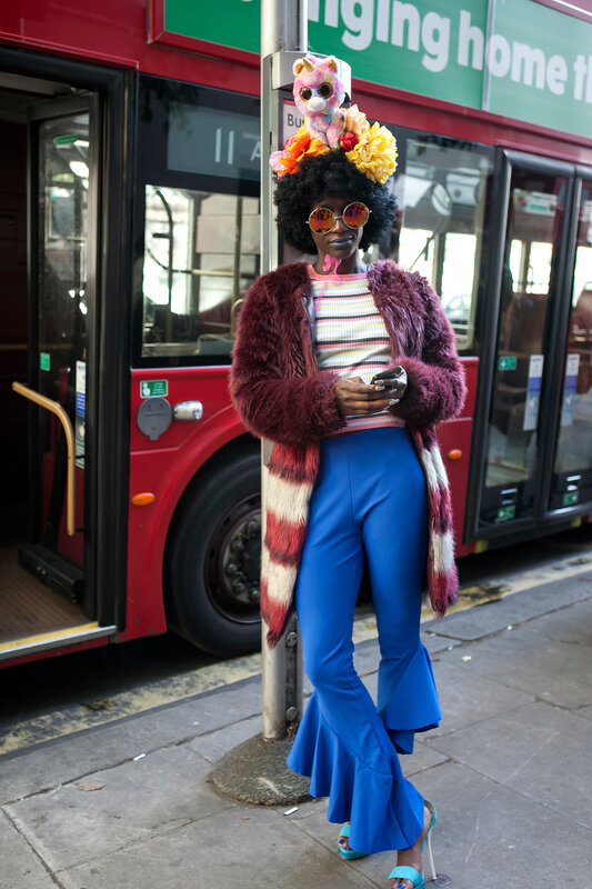 A girl in a claret jacket made of faux fur, blue pants flared in a hat with a toy on her head. London Fashion Week