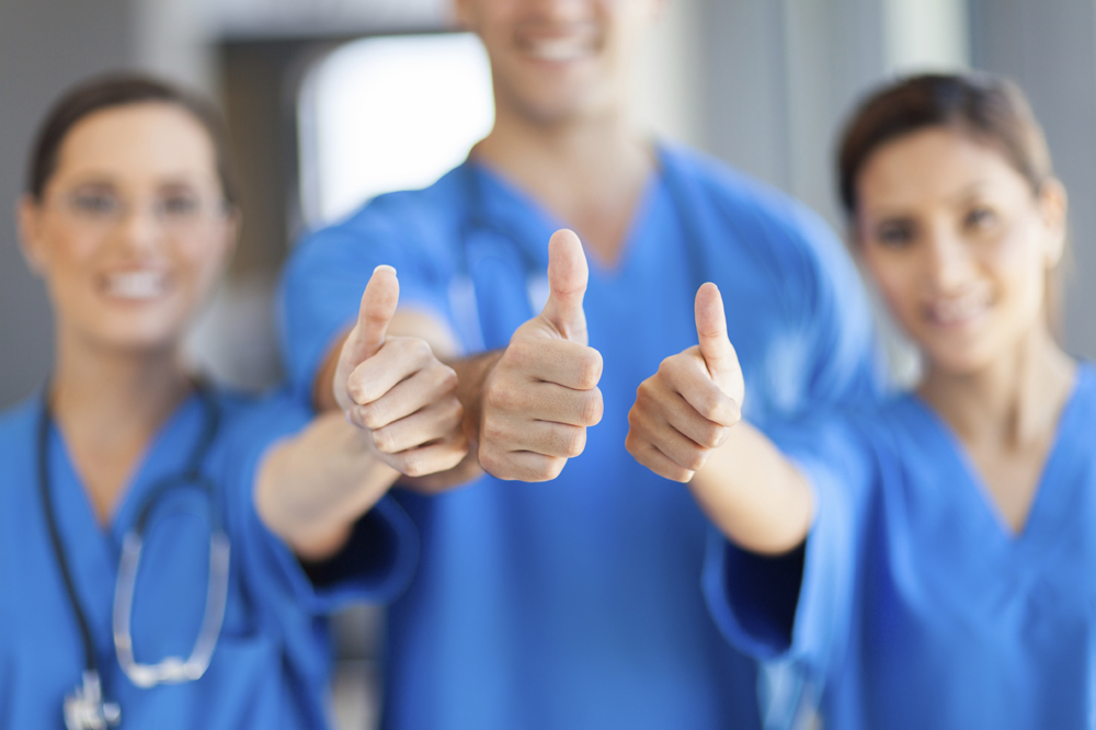 group of healthcare workers thumbs up