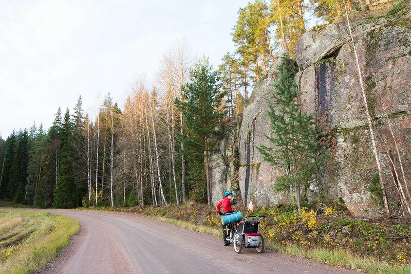 велосипедист и скалы в финляндии у дороги
