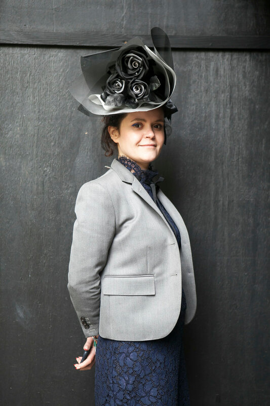 middle-aged woman in a gray jacket and a gray hat with flowers during the London Fashion Week