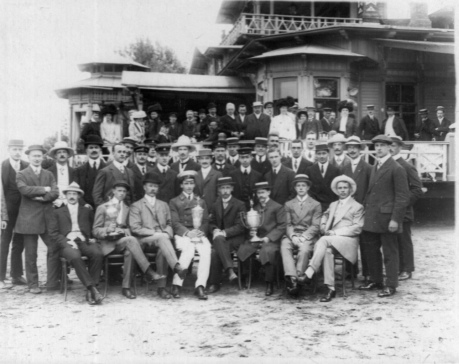 Группа членов общества с призовыми кубками; стоит 1-й справа в кепке М.Кнопмус