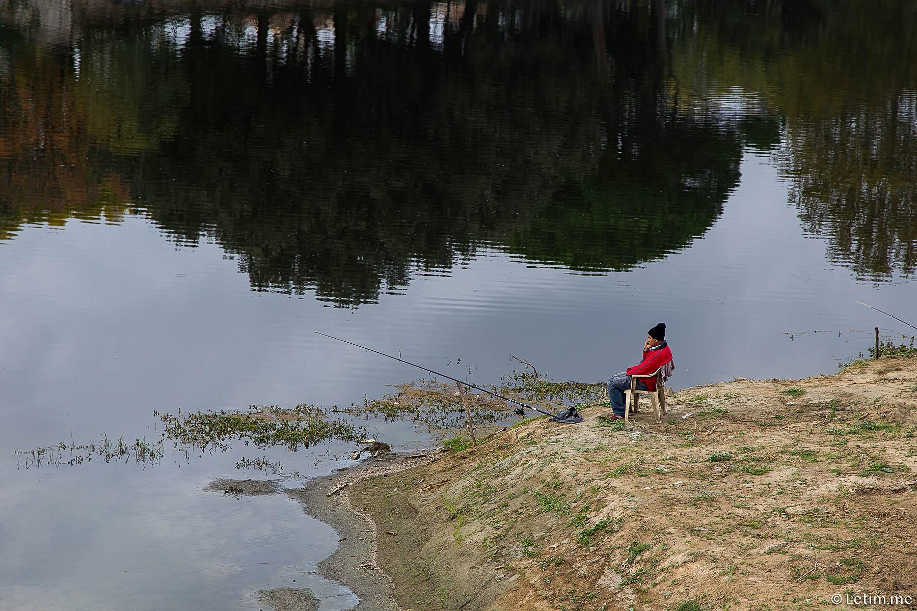 Рыбак во Флоренции на набережной реки Арно