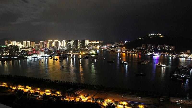 Ночной вид на город Санья с небоскрёба на насыпном острове Феникс. Бухта Санья, остров Хайнань, Китай