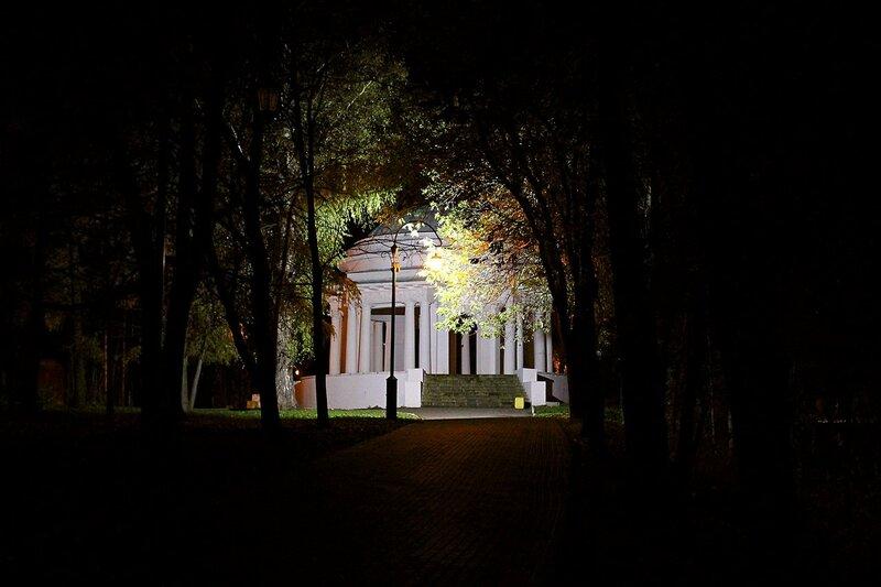 Ротонда в глубине Александровского сада в Кирове ночью: арка среди ночных деревьев, старинный фонарь и белая подсветка